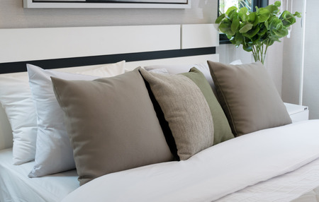 white colour: modern bedroom with brown and green pillow on bed