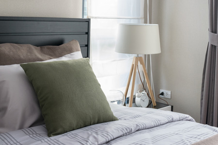 modern bedroom with green pillow and wooden lamp