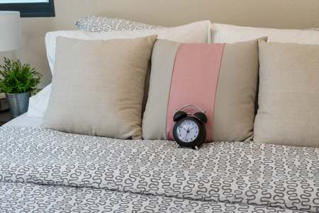 bedspread: close up of pillows and alarm clock on bed Stock Photo