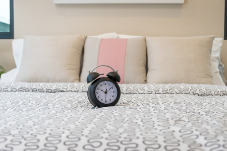 bedchamber: close up of alarm clock on bed in bedroom Stock Photo