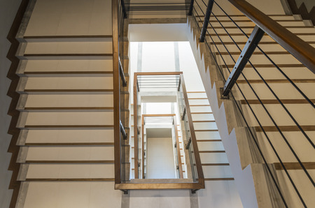 staircase with wooden rail in a modern building photo
