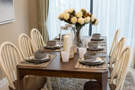 dining room table: dining table and comfortable chairs in modern home with elegant table setting