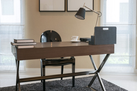 home office interior: wooden table and books in modern working room interior