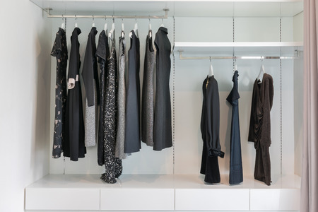 closet: modern closet with row of black dress hanging on coat hanger in wardrobe.