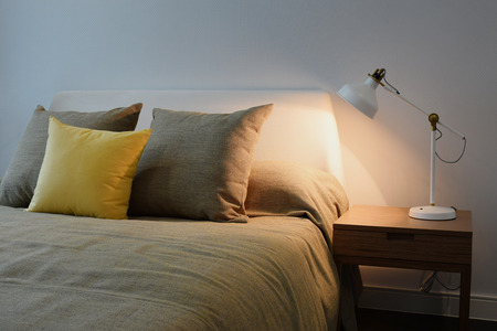 Cozy bedroom interior with pillows and reading lamp on bedside table Stock Photo