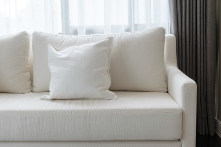 family sofa: white decorative pillows on a casual sofa in the living room Stock Photo