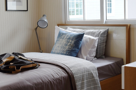 bedside lamp: cozy bedroom interior with pillows and reading lamp on bedside table Stock Photo