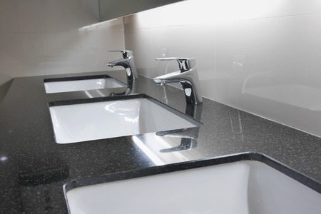 washbasins: white washbasins and faucet on granite counter in restroom Stock Photo
