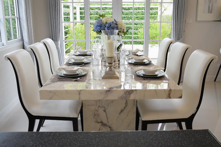banquet table: dining table and comfortable chairs in vintage style with elegant table setting