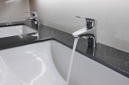 black bathroom: white washbasins and faucet on granite counter with water drop Stock Photo