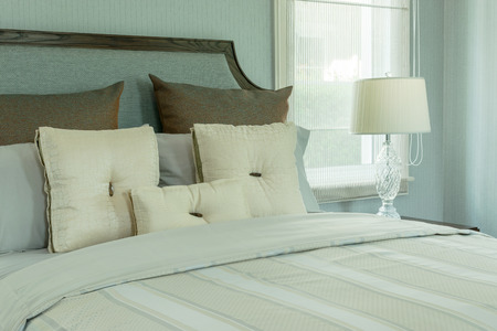 bedside lamp: cozy bedroom interior with white pillows and reading lamp on bedside table