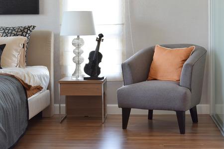 灰色の椅子と自宅のベッドサイド テーブルのランプにオレンジの枕でモダンな寝室のインテリア