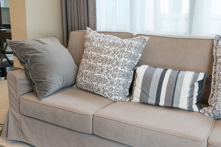 living style: Sturdy brown tweed sofa with grey patterned pillows