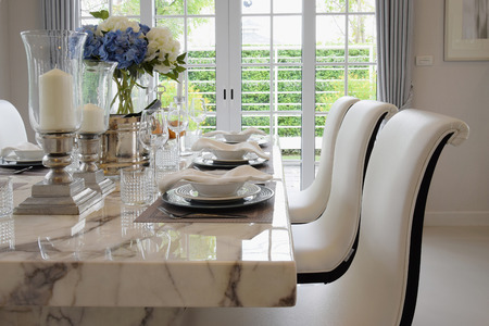 dining table and chairs: dining table and comfortable chairs in vintage style with elegant table setting