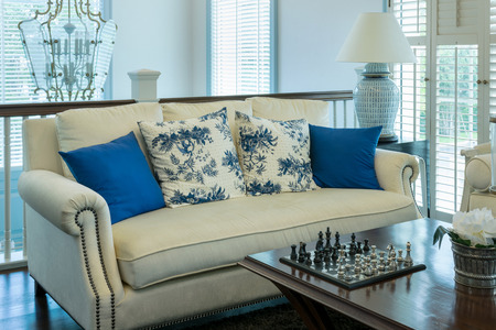 chess piece: luxury living room with blue pattern pillows on sofa and decorative chess board