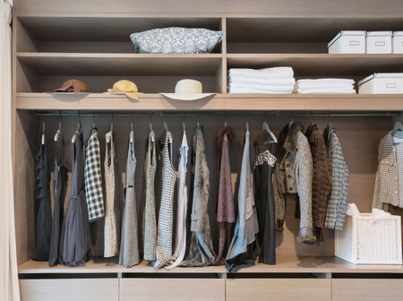 modern closet with row of dress hanging on coat hanger in wardrobe.