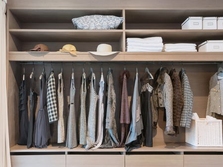 storage: modern closet with row of dress hanging on coat hanger in wardrobe.