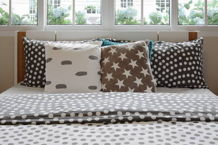 bedside lamp: bedroom interior design with polka dot pillows on bed and decorative bedside table lamp.