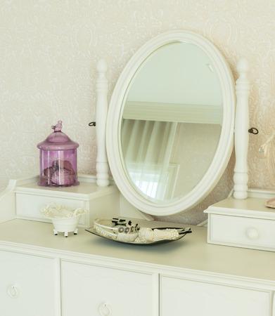 Schönheit und Make-up-Konzept: Spiegel, Schmuck und Make-up-Set auf einem Frisiertisch Standard-Bild