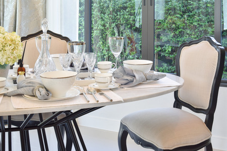 dining room interior: dining table and comfortable chairs in modern home with elegant table setting