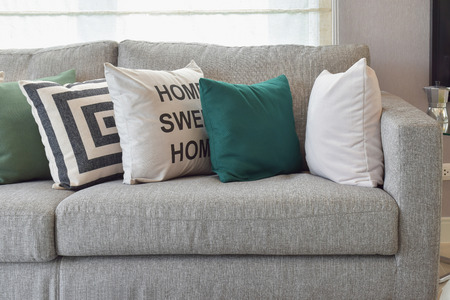 green couch: Retro pillows on the cozy grey sofa in the living room Stock Photo