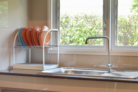 Colorfull plates on shelf next to sink on black marble top with natural light Standard-Bild