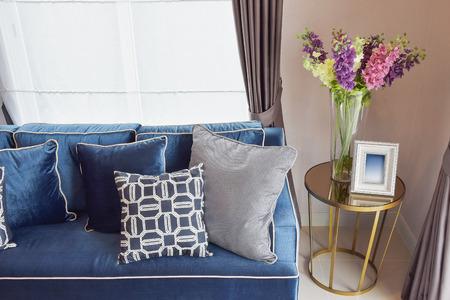 Marineblau klassisches Sofa und Retro-Kissen mit einem schönen Orchidee Vase auf Beistelltisch in Wohnecke Standard-Bild