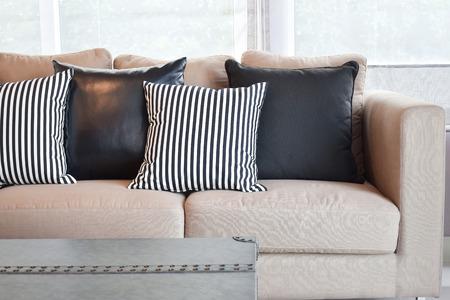 Striped and black leather pillows on velvet beige sofa in modern