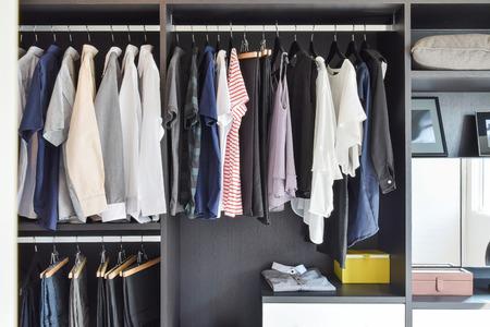 tienda de ropa: armario moderno con la fila de telas que cuelgan en el armario negro Foto de archivo