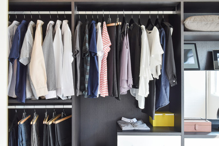 apparel: modern closet with row of cloths hanging in black wardrobe