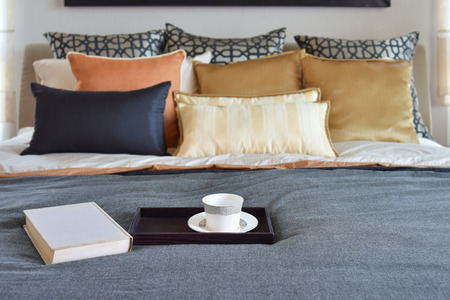 bedroom bed: modern bedroom interior with teacup on decorative wooden tray and white book on the bed
