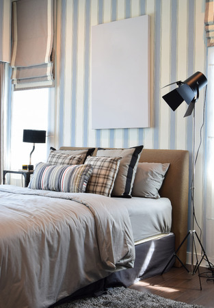 stylish bedroom interior design with striped pillows on bed and decorative table lamp. Stock Photo