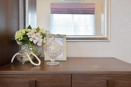 Jewery crystal jar with picture frame and flowers on the wooden table