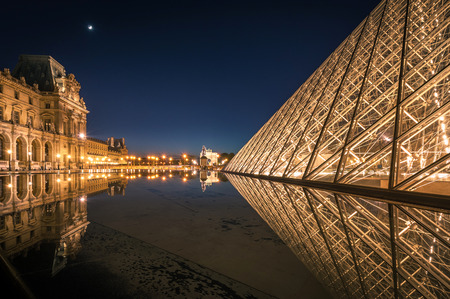 louvre pyramid: Paris, France - April 14, 2013: Reflection of Louvre pyramid shines at dusk. Editorial