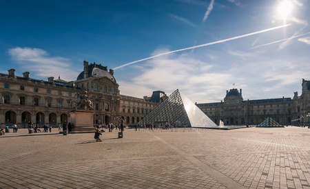 louvre pyramid: Paris, France - April 14, 2013: Tourists in the Louvres central courtyards with the Louvre pyramid and palace.