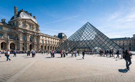 louvre pyramid: Paris, France - April 14, 2013: Tourists in the Louvres central courtyards with the Louvre pyramid and palace. The Louvre is the worlds most visited museum