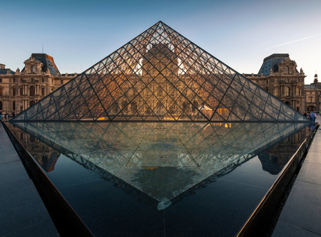Paris, France - April 14, 2013: Louvre museum at sunset. Louvre Museum is one of the worlds largest museums, every year museum visits more than 8 million visitors.