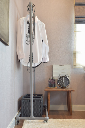 corner clock: white shirts hanging on standing rail and decorative alarm clock in industrial style dressing corner
