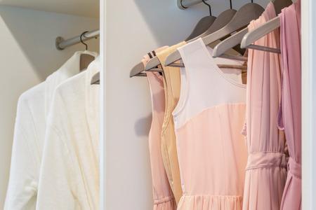 Reihe der bunten Kleid hängen Kleiderbügel in weißen Kleiderschrank