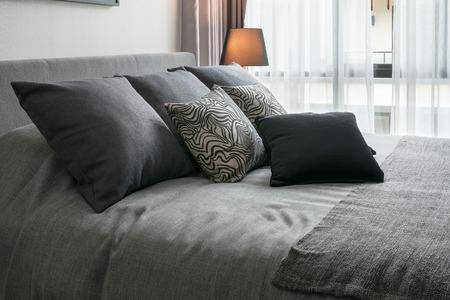elegante diseño interior del dormitorio con almohadas estampadas negras en la cama y la lámpara de mesa decorativo. Foto de archivo