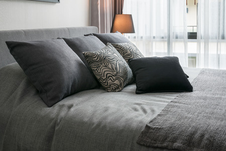 bed sheets: stylish bedroom interior design with black patterned pillows on bed and decorative table lamp. Stock Photo