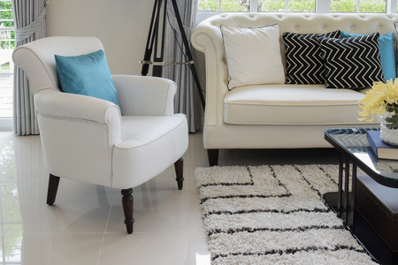 vintage living room: white and blue pillows on a white leather couch in vintage living room Stock Photo