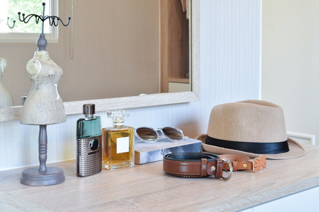 fragrance: brown hat ,perfume and leather belt on a wooden dressing table Stock Photo