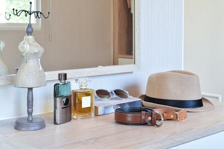 bruine hoed, parfum en lederen riem op een houten kaptafel Stockfoto