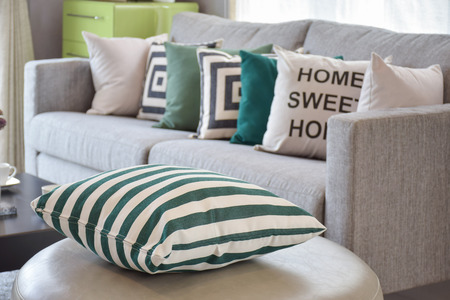 furnished: green striped pillows on the cozy grey sofa in the living room