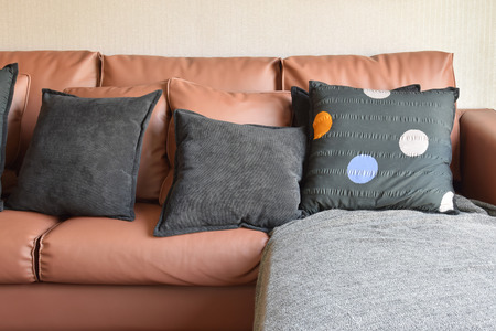 brown leather sofa: modern living room design with brown leather sofa and black pillows