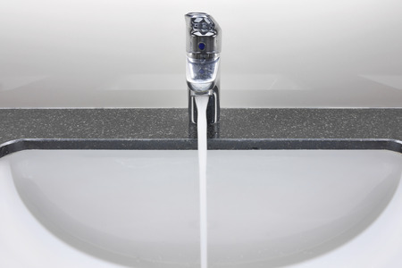 granite counter: white washbasin and faucet on granite counter with water drop Stock Photo