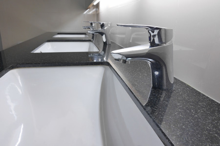 white washbasins and faucet on granite counter in restroom Stock Photo