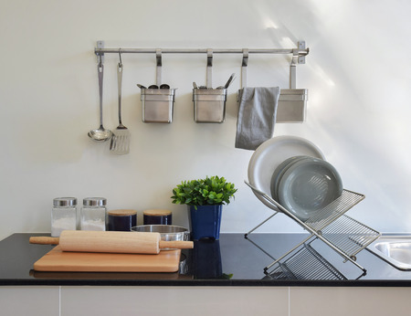 counter top: modern ceramic kitchenware and utensils on the black granite counter top