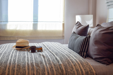 wooden bed: stylish bedroom interior design with striped pillows on bed and decorative table lamp. Stock Photo
